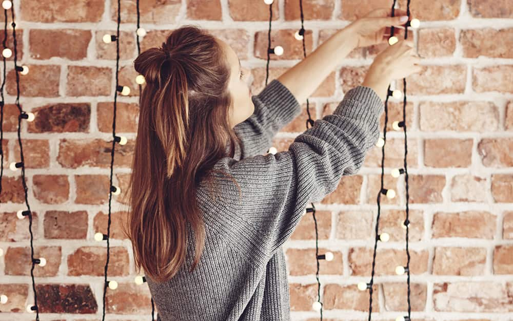 A woman hanging string lights on a brick exterior
