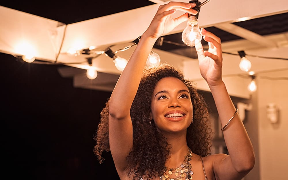 A woman hanging outdoor string lights on a deck