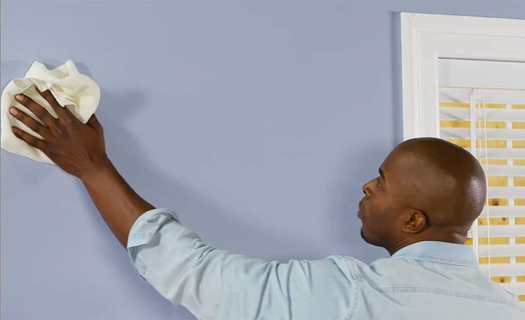 Man wiping down a wall's surface.