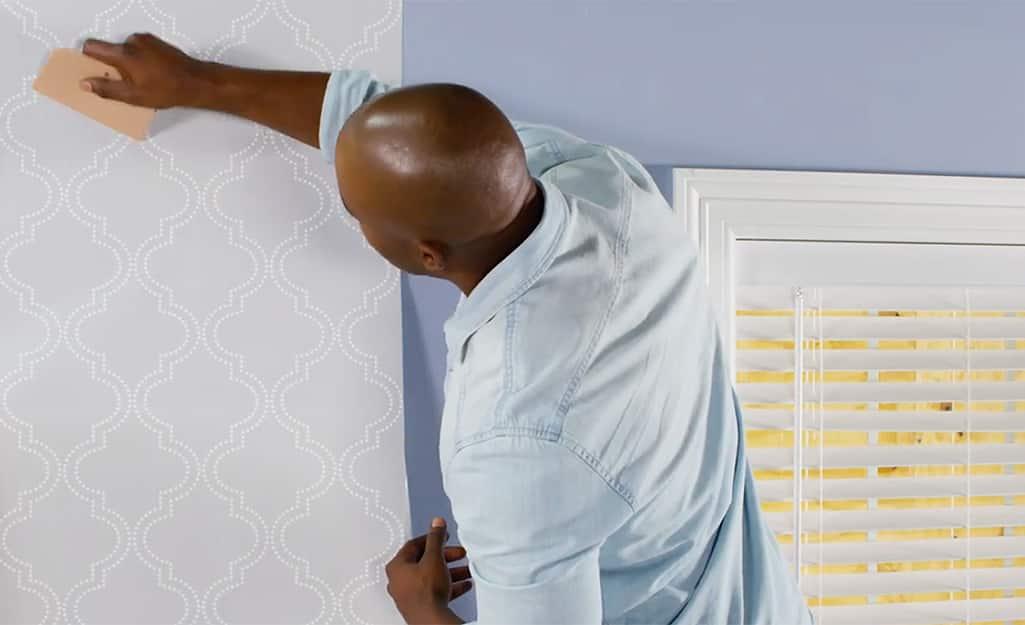 Man smoothing down wallpaper.