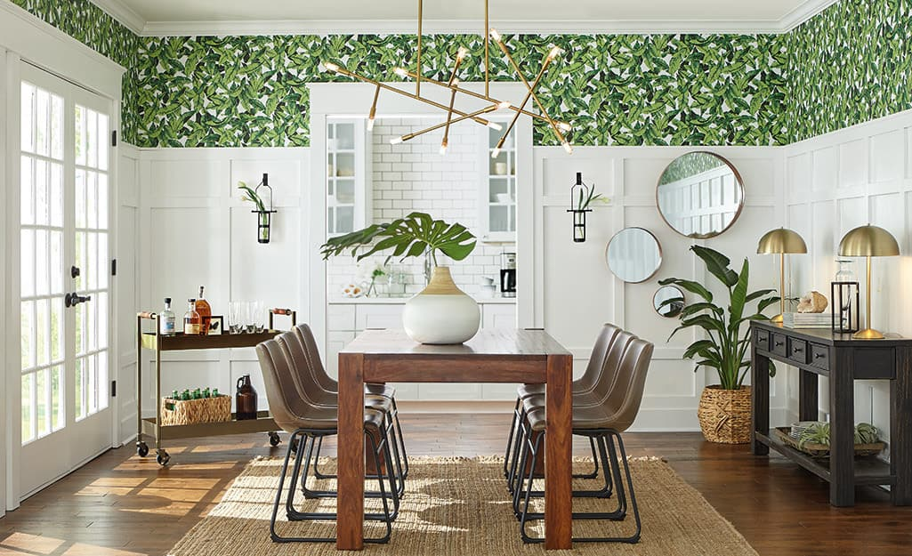A dining room with botanical wallpaper.