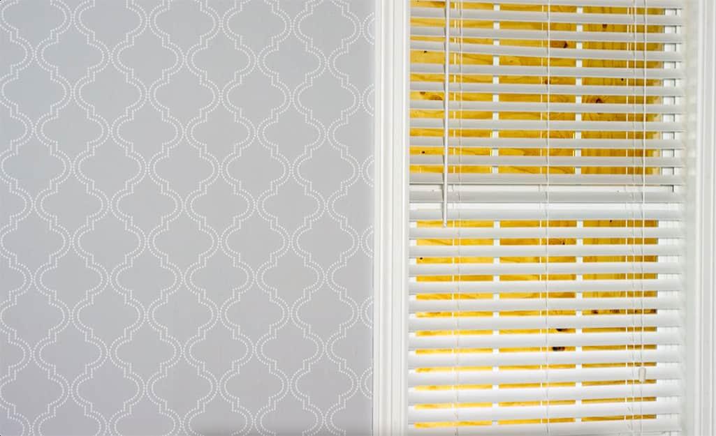 Freshly hung wallpaper applied near a window.