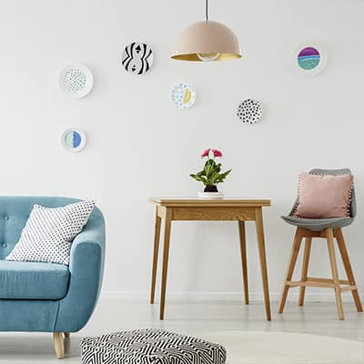 Decorative plates hung on a wall with a couch, table and chair nearby.