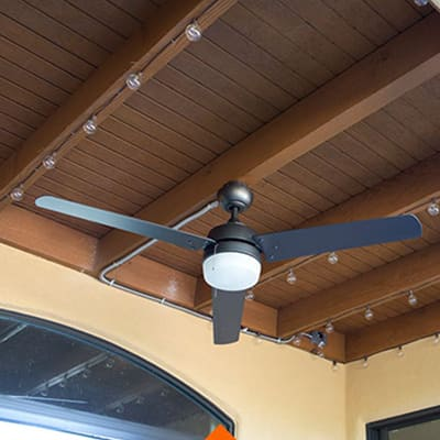 A brown outdoor ceiling with a fan and string lights.