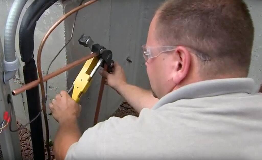 A man cutting a pipe