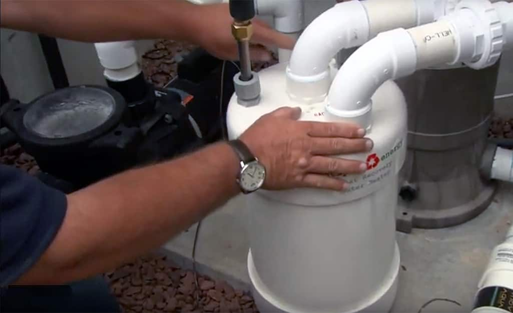 A man touching the refrigerant tank for a swimming pool