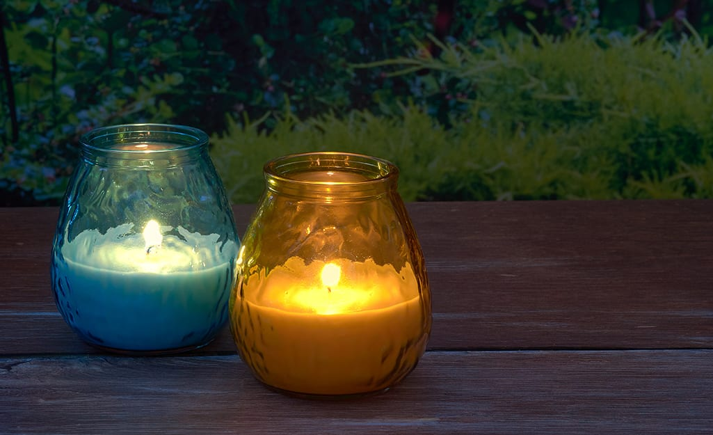 Candles on a wood table in a backyard.