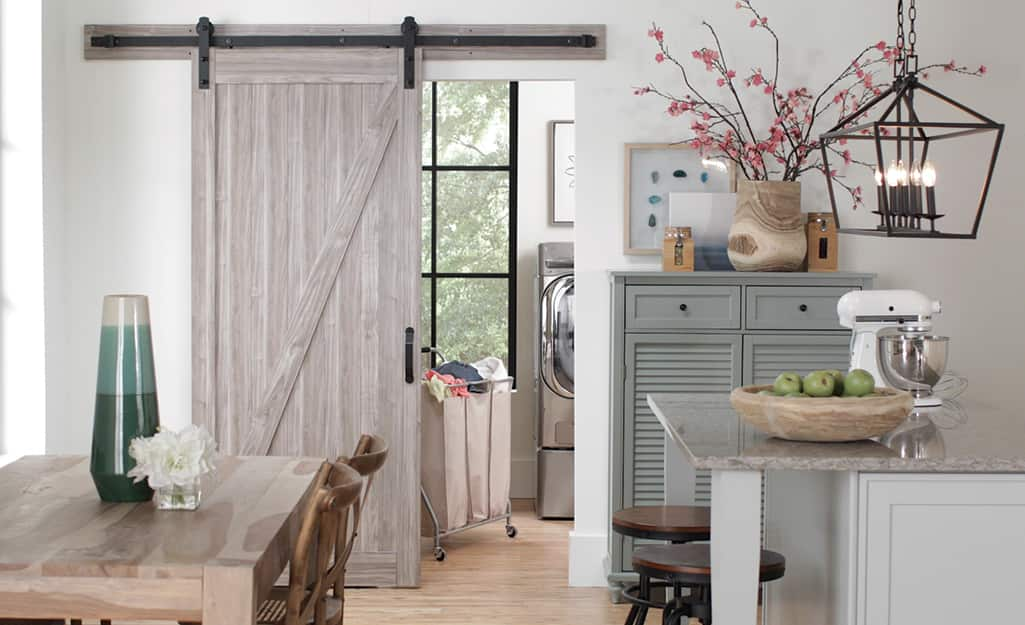A barn door separating a kitchen from a laundry room.