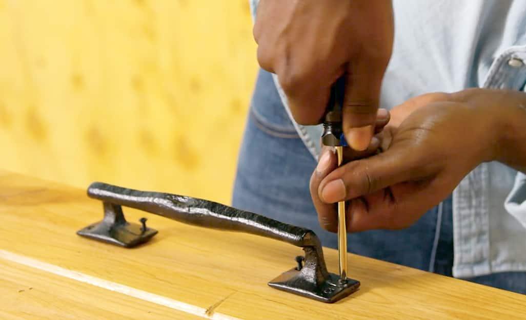 A man screwing a door handle to a barn door.