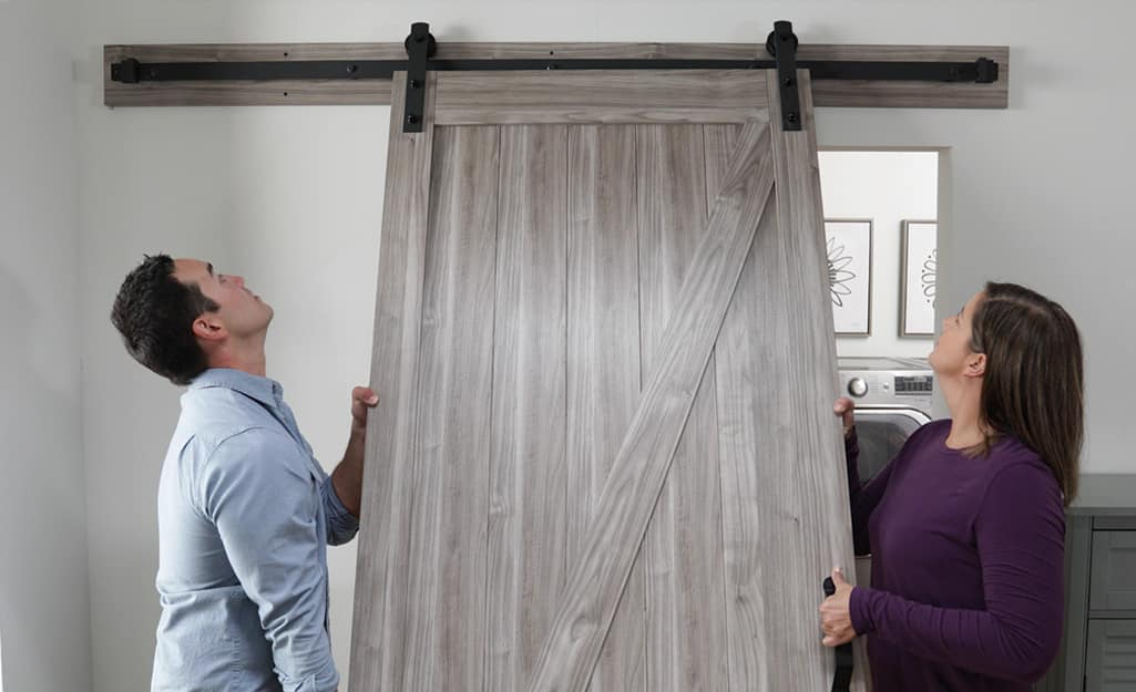 A man and a woman lifting and hanging a barn door on its metal track.