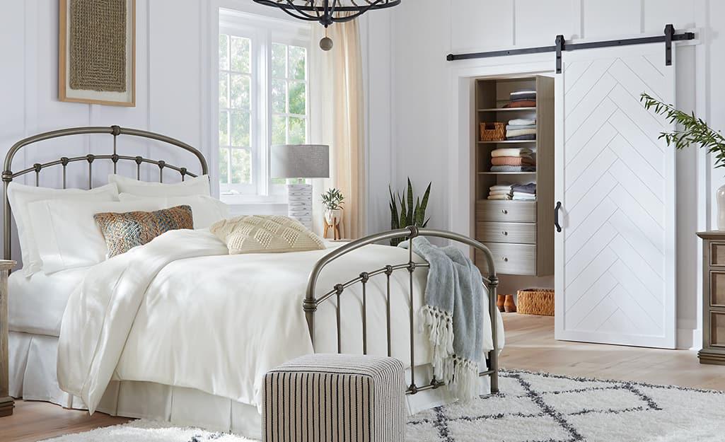 A white barn door installed as a bedroom closet door.