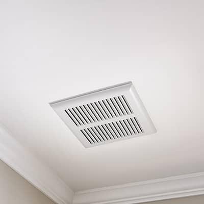 A bathroom fan installed in the ceiling of a bathroom.