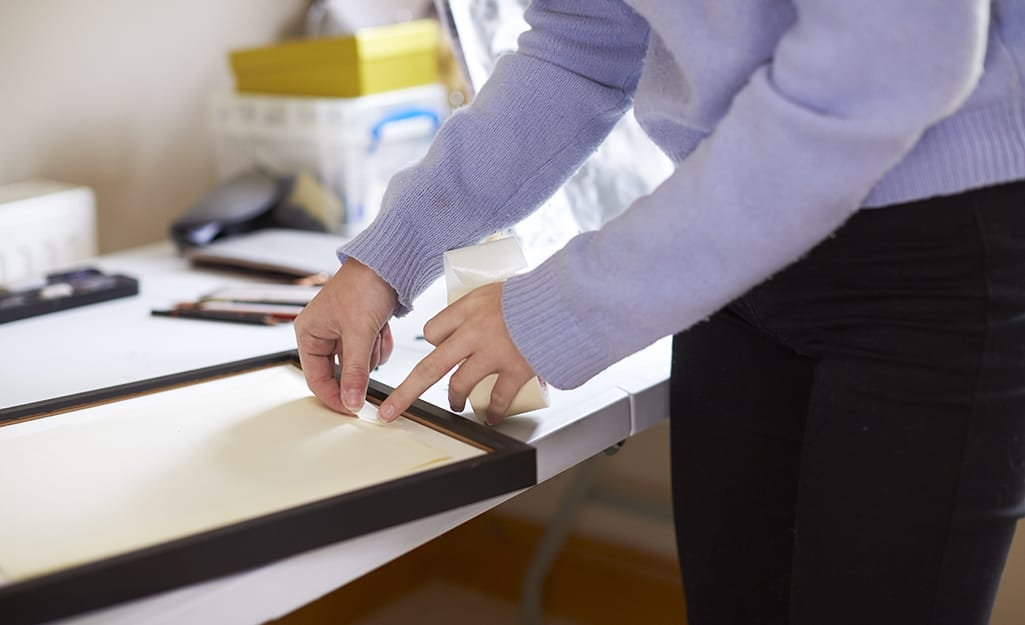 A person preparing a small frame to hold a mirror.