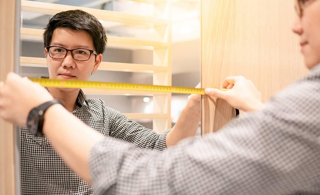 A person measuring a frameless mirror.