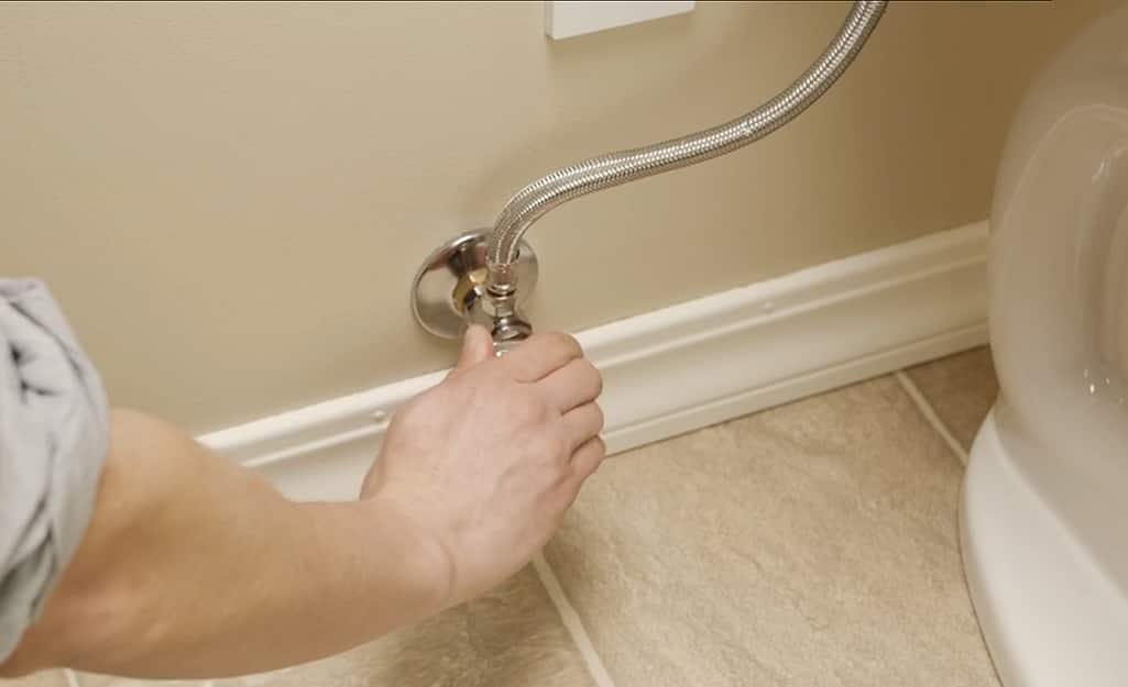 A person stops the flow of water to a toilet from the wall shut-off valve.