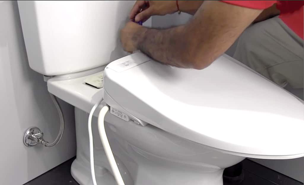 A person hooks up the water supply hose to the back of a bidet toilet seat.