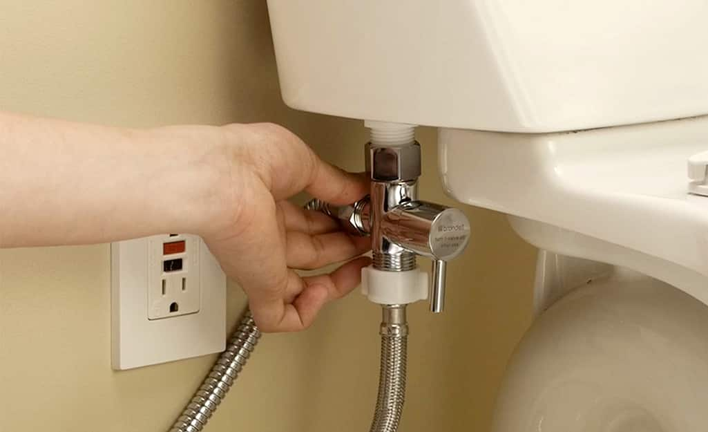 A person attaches a hand-held bidet valve to the base of a toilet tank.