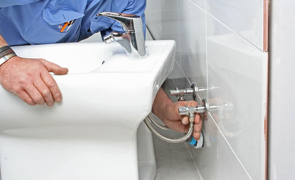 A person installs a freestanding bidet to wall-mounted plumbing fixtures.