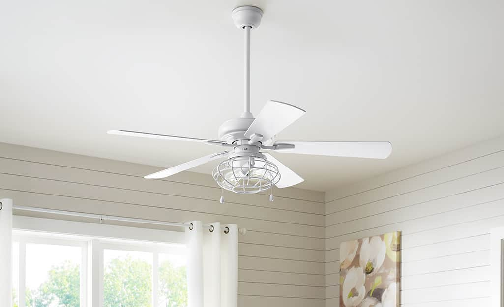 A white ceiling fan hanging in a room.
