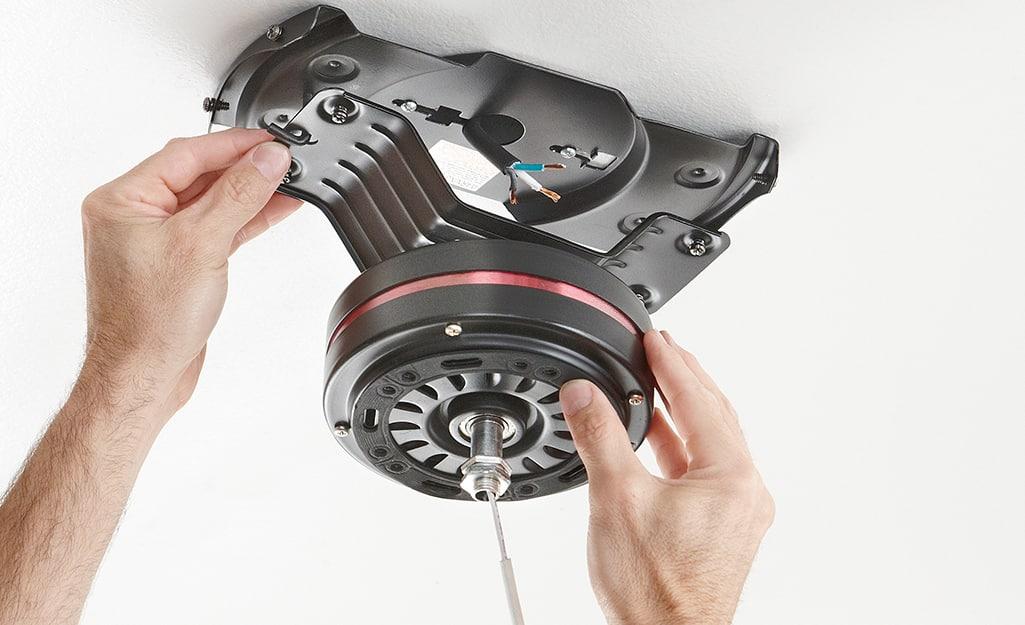 A person mounting a fan bracket.