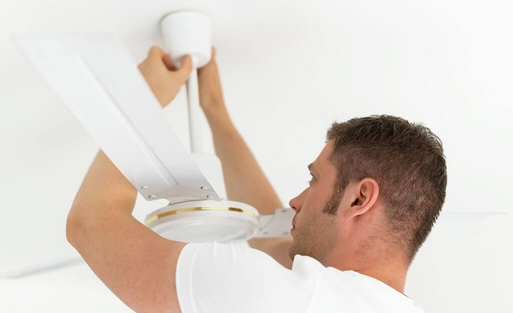 A man mounting a ceiling fan downrod.