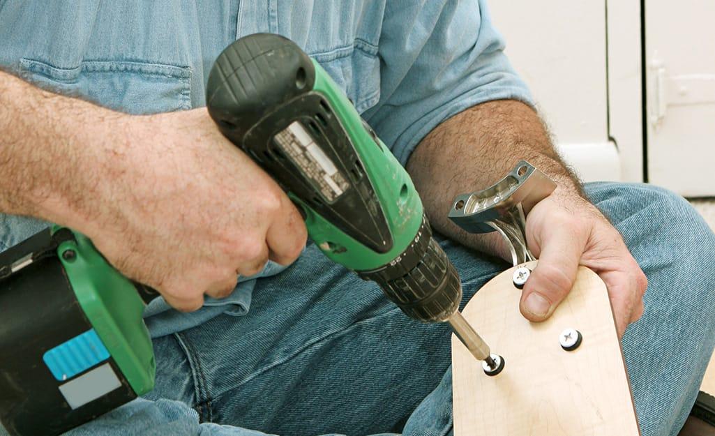 A man attaches blades to a ceiling fan.
