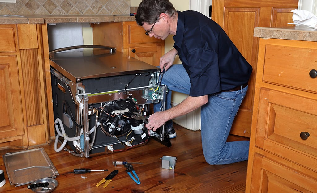 A person using a hole saw for installing dishwasher supply lines.