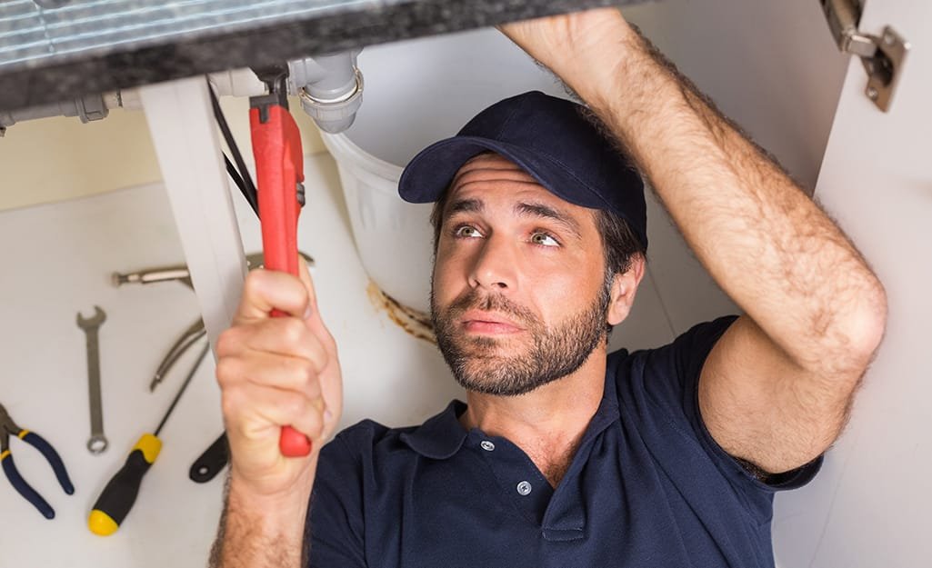 A person using an adjustable wrench on a water line for dishwasher installation.