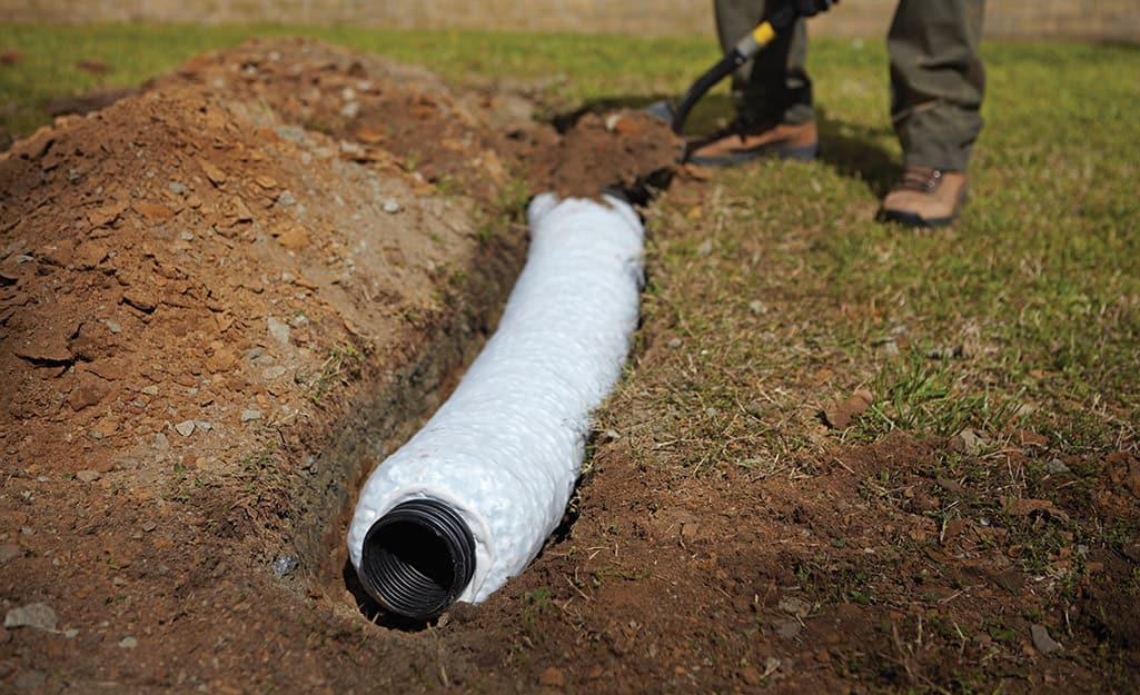 A person installing a gravel-free French drainage system.
