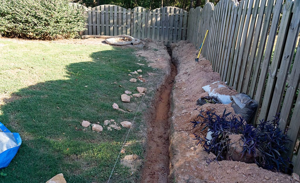 A French drain trench dug along the edge of a fenced-in yard.
