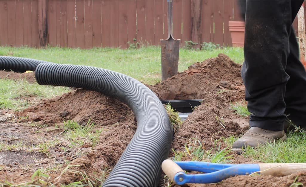 French drain pipe partially laid in a trench.