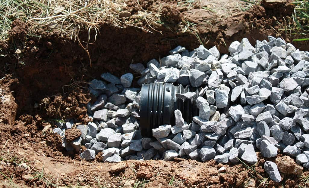 A French drain pipe opening peaking out of a mound of gravel.