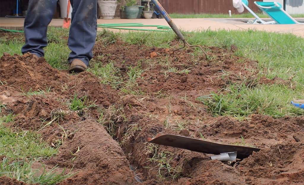 A person filling a trench with topsoil.