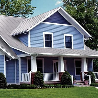 A blue home with a gray metal roof.