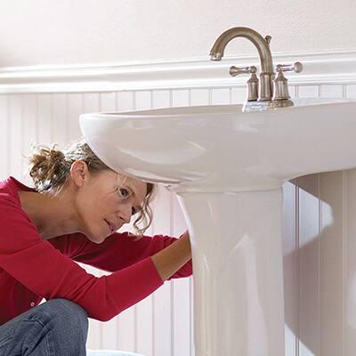 A woman installing a pedestal sink.