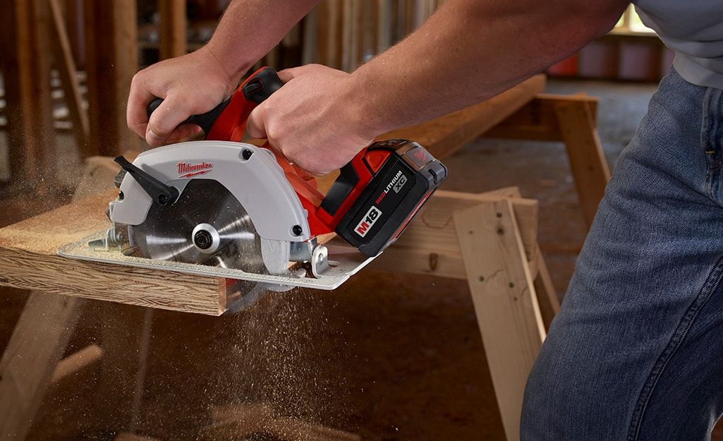 A person uses a circular saw to cut a board.