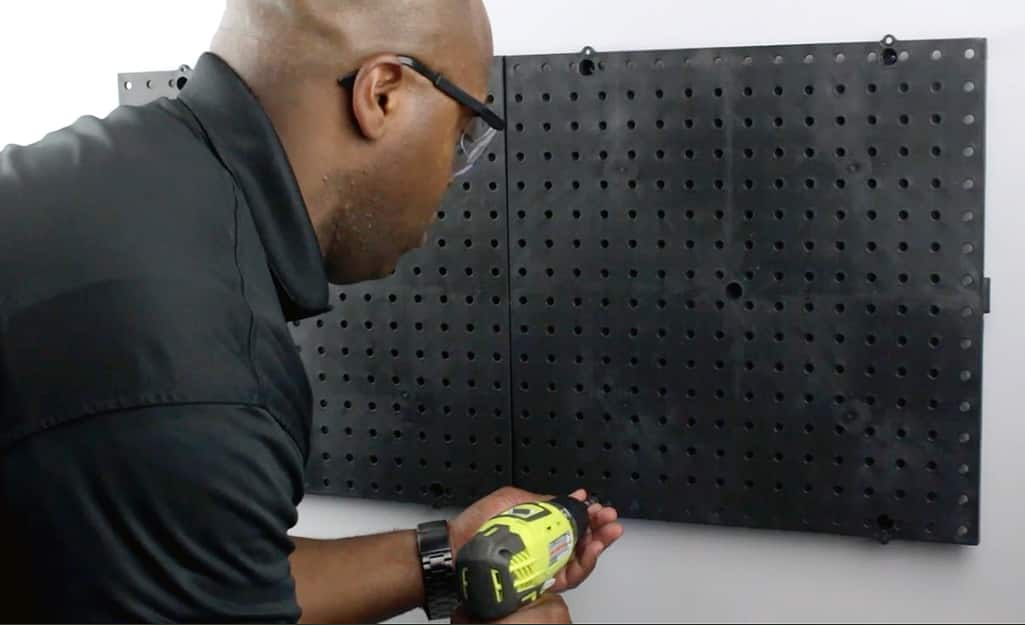 A person uses a power drill to drill holes for hanging a pegboard.
