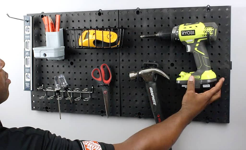 A person hangs tools on a pegboard.