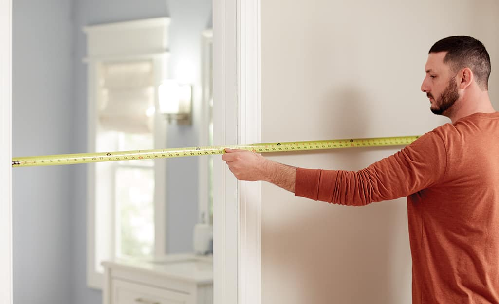 A man measure a doorway using a tape measure.