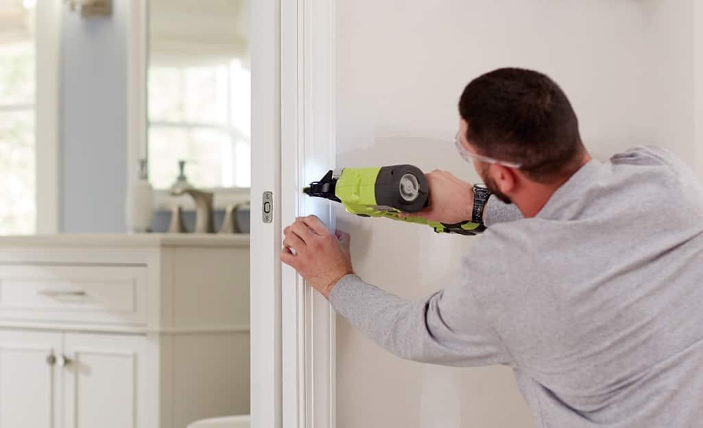 Man installs door trim around the pocket door.