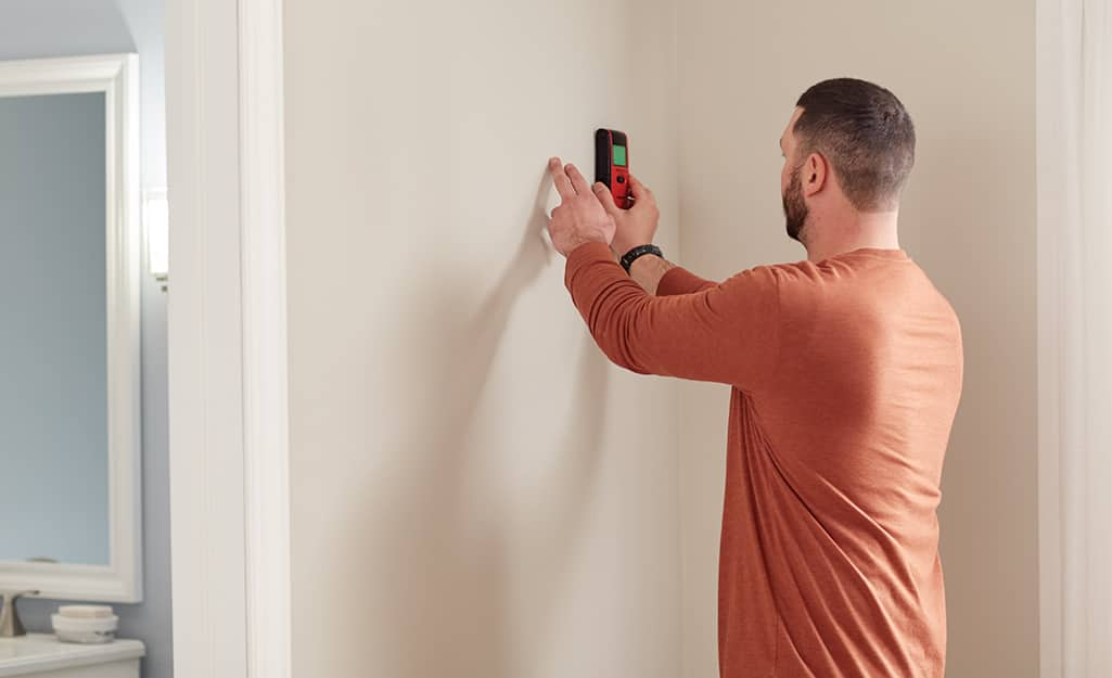 A man uses a stud finder to determine if a wall is load bearing.