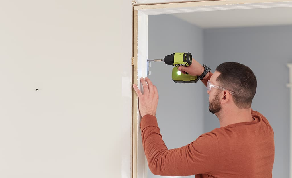 A man removes the old door and frame.