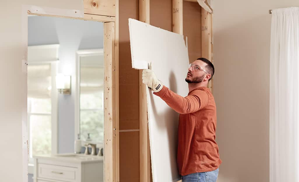 A man removes drywall.