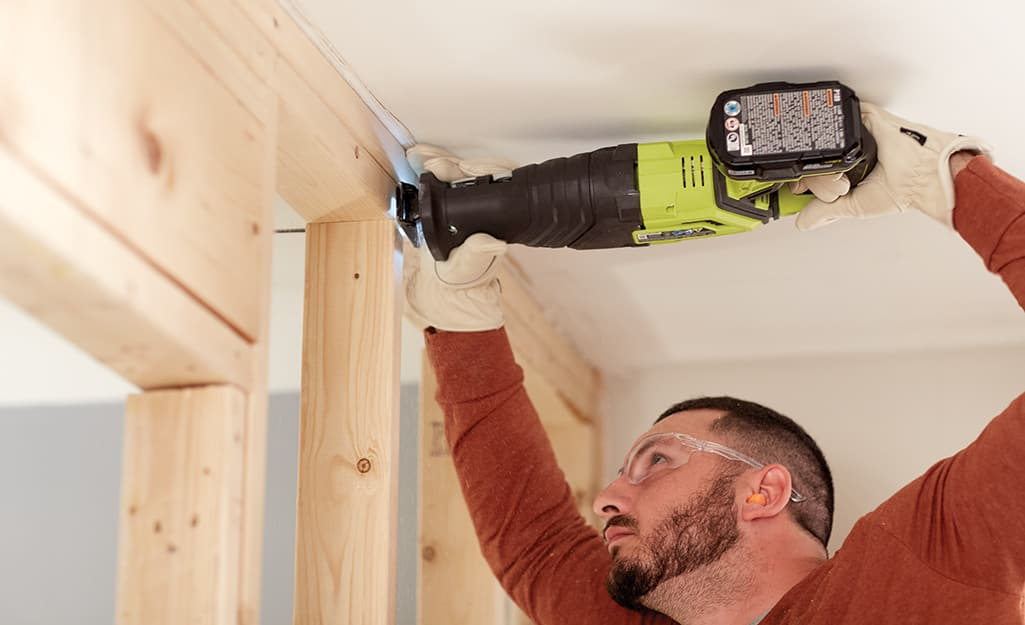 A man uses a saw to cut studs in a wall.