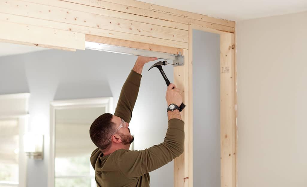 A man uses a hammer to install pocket door track.