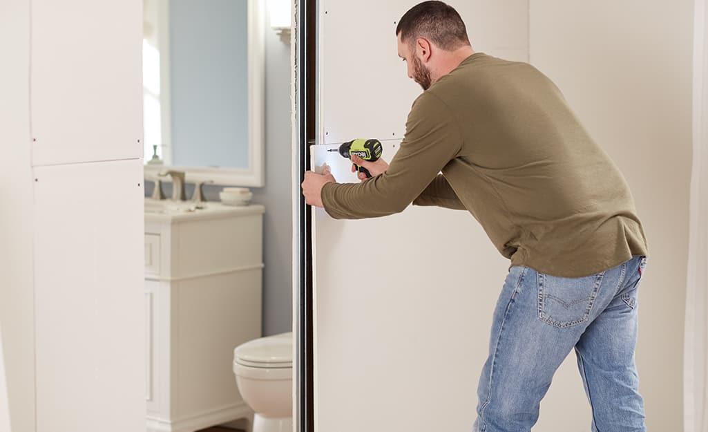 A man repairs the drywall.