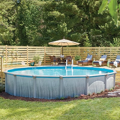An above ground pool next to an elevated deck with lounge furniture.