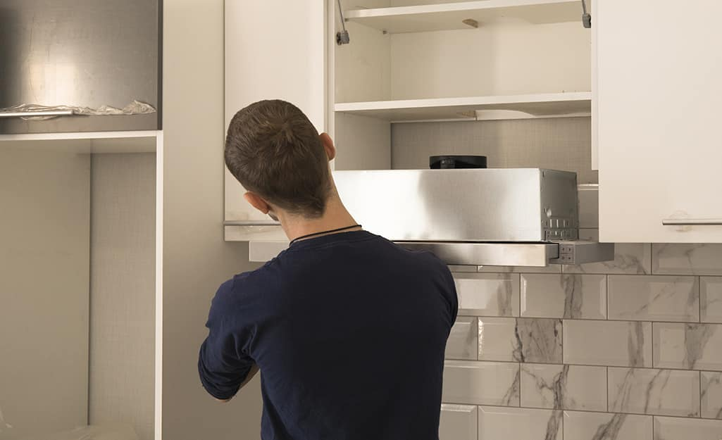 A person removes a range hood from over a stovetop.