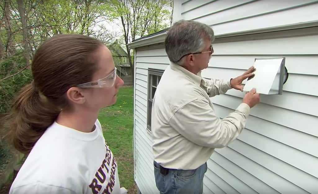 A person installs a duct cap from the outside of a house.