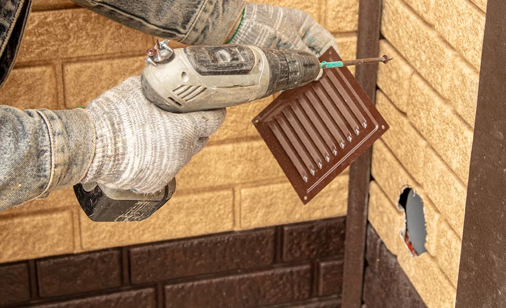 A person installs a vent cover to an exterior brick wall.